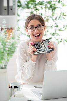 Sonriente a feliz joven en vasos con calculadora en la oficina. equilibrio exitoso.