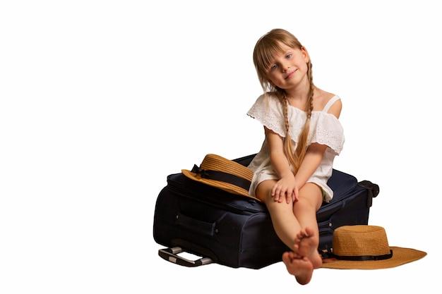 Sonriente, feliz niña sentada en una maleta de equipaje, bolsa de viaje en una habitación de hotel