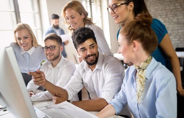 Sonriente gente de diseño trabajando juntos en un escritorio en la computadora en la oficina