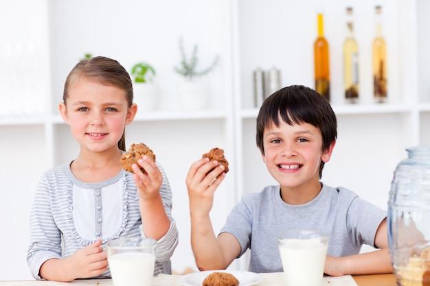 Sonriente hermano y hermana comiendo galletas y bebiendo leche