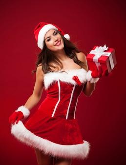 Sonriente y hermosa mujer sosteniendo pequeño regalo de navidad rojo