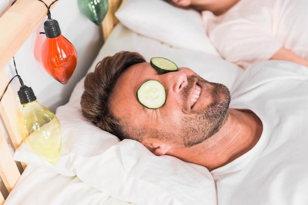 Sonriente hombre acostado en la cama con rodaja de pepino sobre los ojos