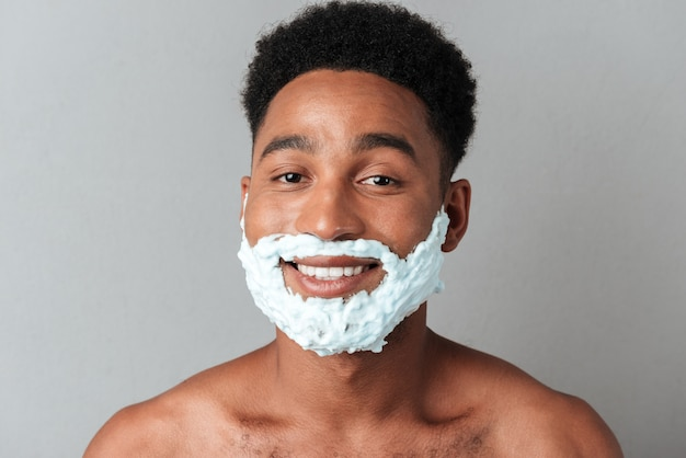 Sonriente hombre africano desnudo con cara en espuma de afeitar