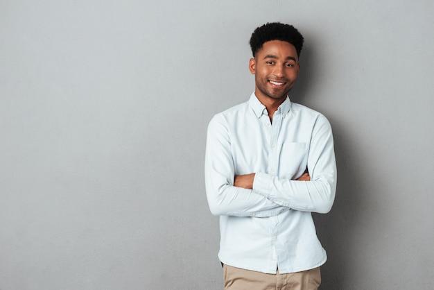 Sonriente hombre africano de pie con los brazos cruzados