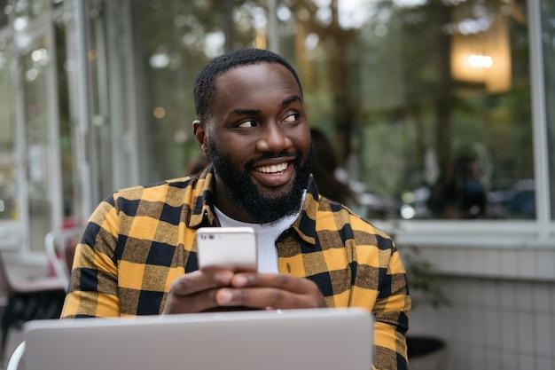 Sonriente hombre africano con smartphone, trabajando en línea. retrato de joven desarrollador exitoso planificación puesta en marcha, sentado en el lugar de trabajo.