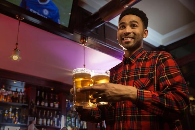 Sonriente hombre afroamericano llevando vasos de cerveza