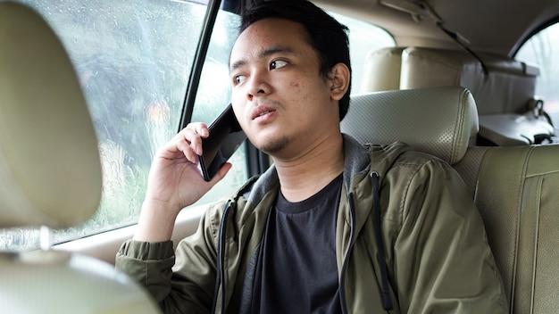 Sonriente hombre asiático en un coche mientras habla por teléfono