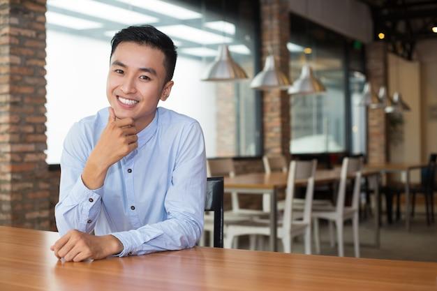Sonriente hombre asiático hermoso sentado en el café vacía