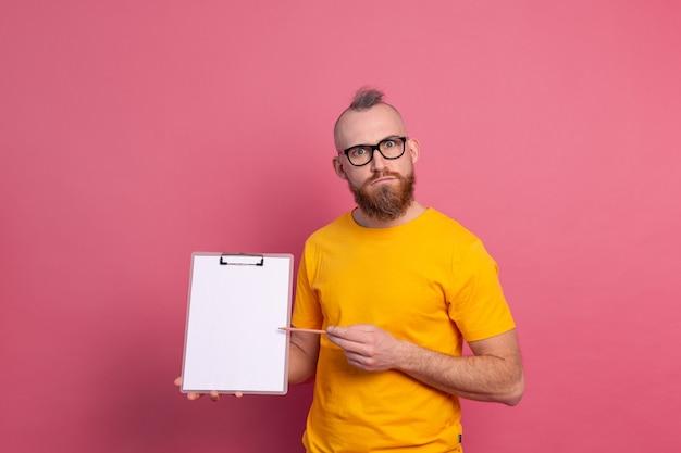 Sonriente hombre barbudo con anteojos vistiendo ropa casual sosteniendo un portapapeles con un papel en blanco apuntando