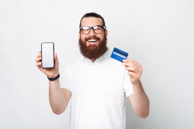 Sonriente hombre barbudo con gafas está mostrando a la cámara la pantalla del teléfono y la tarjeta que está usando.