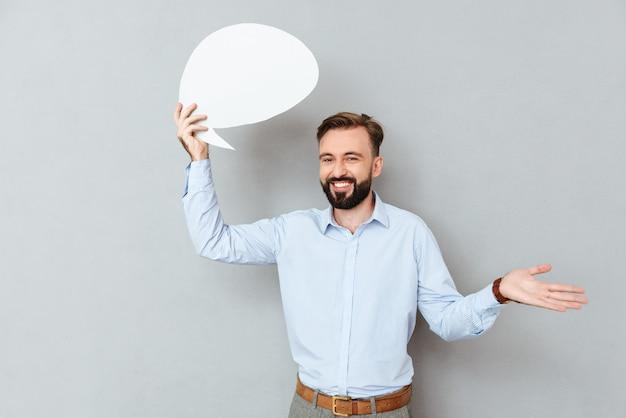 Sonriente hombre barbudo en ropa de negocios con bocadillo en blanco