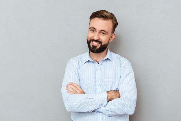 Sonriente hombre barbudo en ropa de negocios con los brazos cruzados
