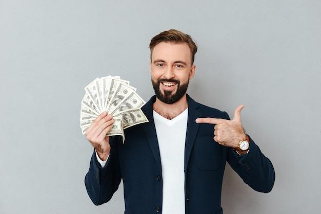 Sonriente hombre barbudo en ropa de negocios con dinero y apuntando a su mientras mira a la cámara sobre gris