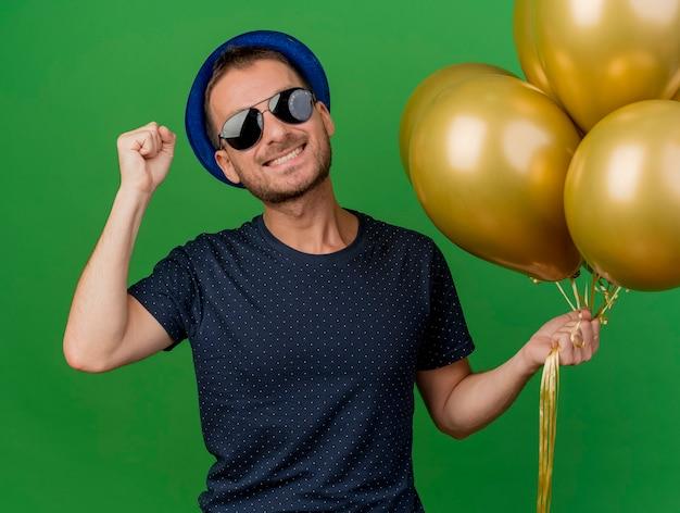 Sonriente hombre caucásico guapo en gafas de sol con sombrero de fiesta azul mantiene el puño y sostiene globos de helio aislados sobre fondo verde con espacio de copia