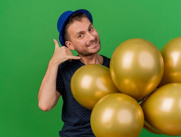 Sonriente hombre caucásico guapo con gestos de sombrero de fiesta azul me llaman firmar y sostiene globos de helio aislados sobre fondo verde con espacio de copia
