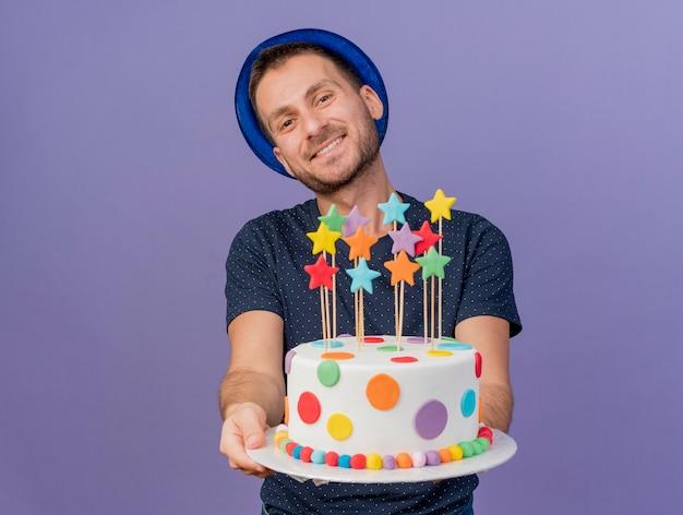 Sonriente hombre caucásico guapo con sombrero azul sostiene la torta de cumpleaños mirando a cámara aislada sobre fondo púrpura con espacio de copia