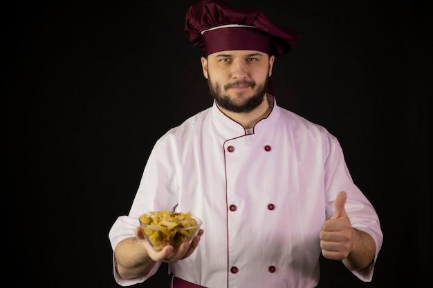 Sonriente hombre chef en uniforme tiene tazón con varias pastas secas que muestra como signo