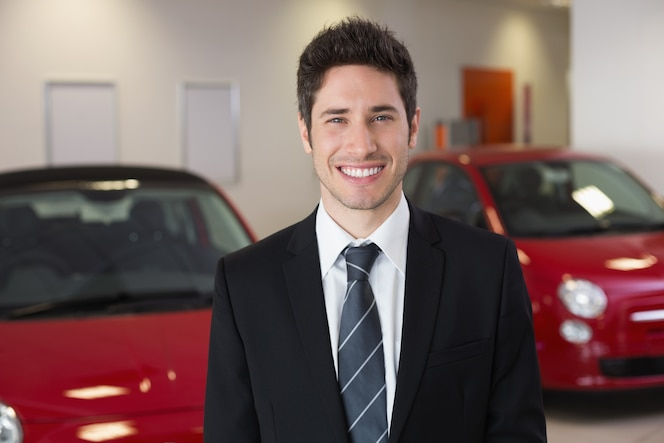 Sonriente hombre de negocios de pie junto a un coche en el nuevo showroom de automóviles