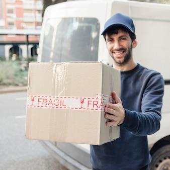 Sonriente hombre de entrega con caja de cartón