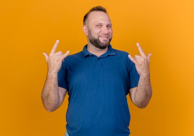 Sonriente hombre eslavo adulto haciendo signos de rock aislados en la pared naranja