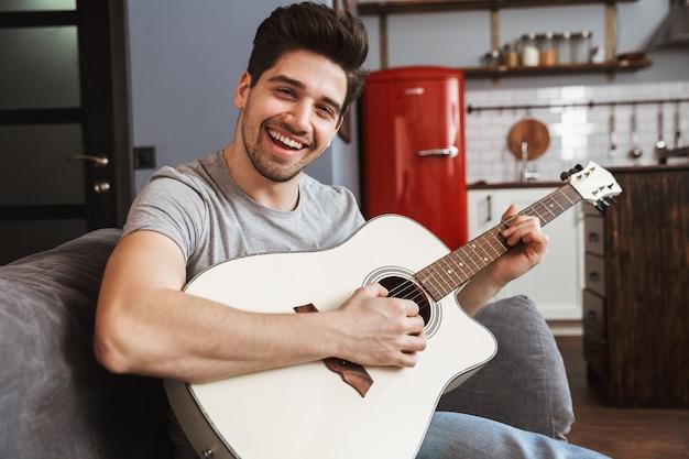 Sonriente hombre guapo de 30 años sentado en el sofá en casa y tocando música en la guitarra acústica