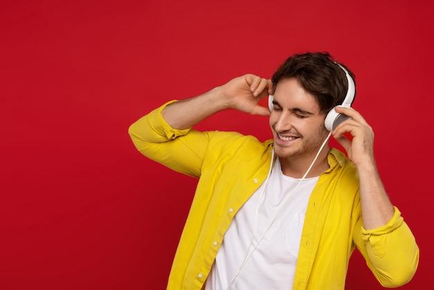 Sonriente hombre guapo en camisa amarilla escuchando música en auriculares con los ojos cerrados, hace movimientos a la música, estar en alto espíritu
