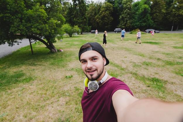 Sonriente hombre haciendo selfie en el parque