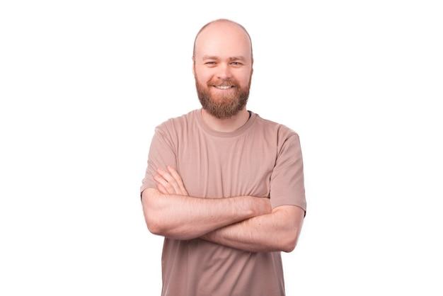 Sonriente hombre hipster barbudo de pie en blanco con los brazos cruzados