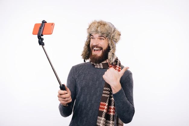 Sonriente hombre hipster barbudo en ropa de invierno tomando selfie sobre fondo blanco.