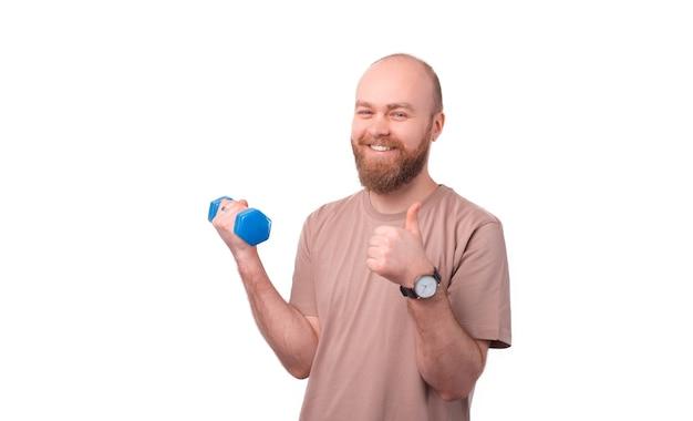Sonriente hombre hipster barbudo en trabajo informal con mancuernas y mostrando el pulgar hacia arriba