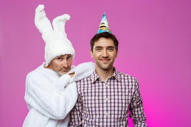 Sonriente hombre y hombre en traje de conejo en la fiesta de cumpleaños sobre pared púrpura.