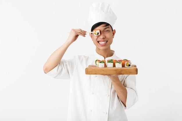 Sonriente hombre jefe chino en uniforme de cocinero blanco sosteniendo un plato y comiendo sushi con palillos aislados sobre la pared blanca