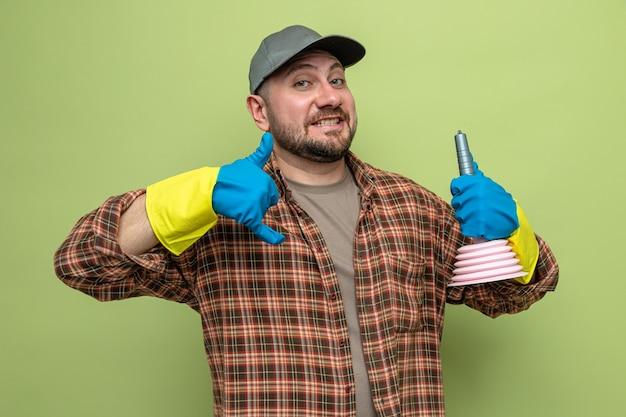Sonriente hombre limpiador eslavo con guantes de goma sosteniendo el émbolo de goma y gesticulando llámame señal