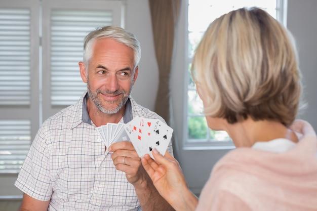 Sonriente hombre maduro jugando a las cartas con la mujer en casa