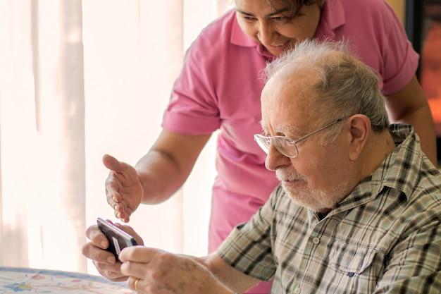 Sonriente hombre mayor y cuidador con smartphone están haciendo una videollamada