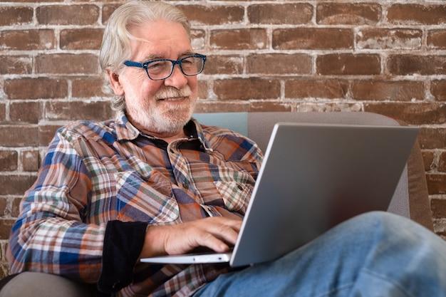 Sonriente hombre mayor relajado sentado en casa en un sillón con ordenador portátil pared de ladrillo