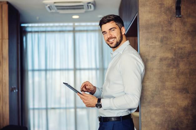 Sonriente hombre de mediana edad de pie contra la pared y usando una tableta para ver las noticias.