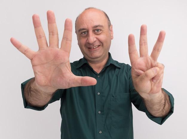 Sonriente hombre de mediana edad vestido con camiseta verde mostrando diferentes números aislados en la pared blanca