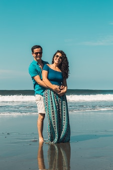 Sonriente hombre y mujer abrazando en el paseo marítimo de la playa