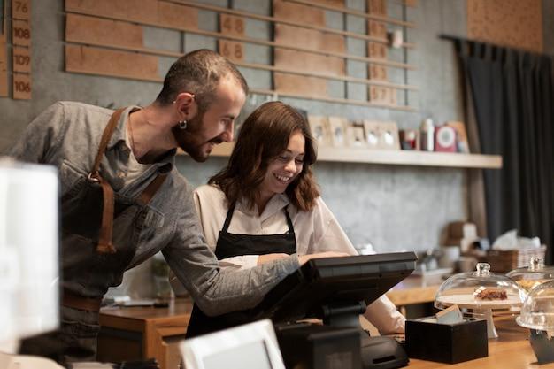 Sonriente hombre y mujer en caja registradora