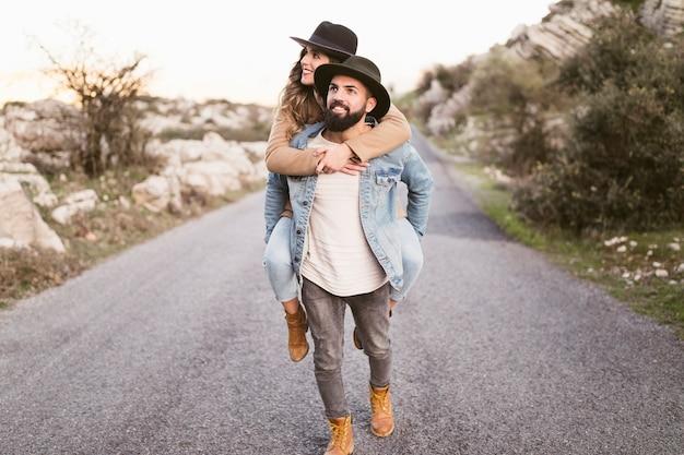 Sonriente hombre y mujer en una carretera de montaña mirando a otro lado