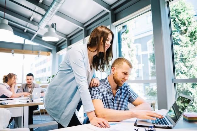 Sonriente hombre y mujer cooperando en la computadora portátil