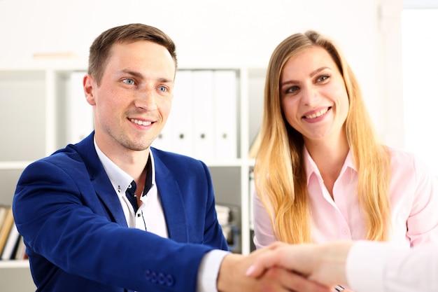 Sonriente hombre y mujer se dan la mano como hola en la oficina