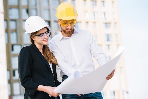 Sonriente hombre y mujer mirando blueprint