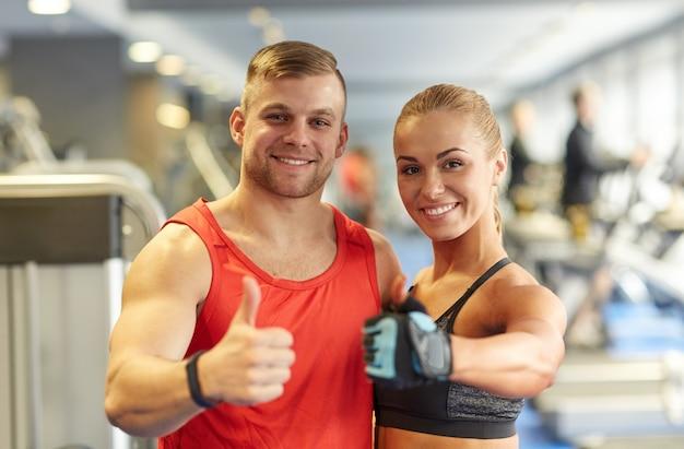 Sonriente hombre y mujer mostrando los pulgares para arriba en el gimnasio