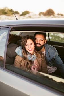 Sonriente hombre y mujer sentada en los asientos traseros