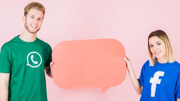 Sonriente hombre y mujer sosteniendo el bocadillo de diálogo naranja vacío