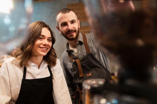 Sonriente hombre y mujer trabajando en cafetería