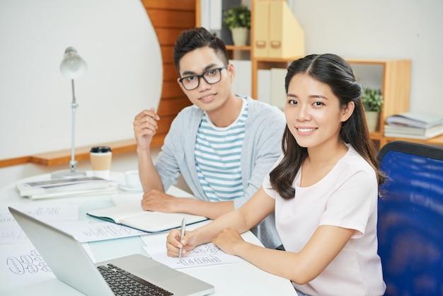 Sonriente hombre y mujer de trabajo en el escritorio