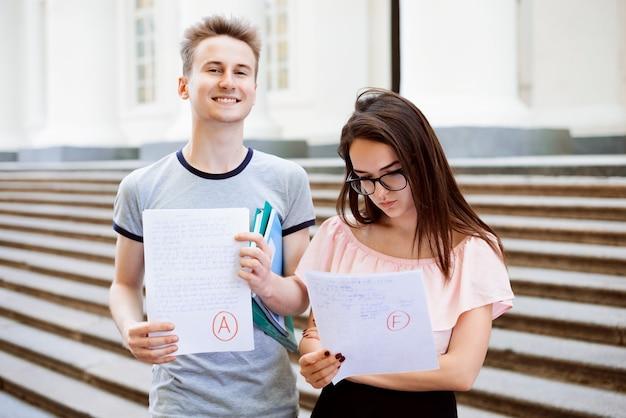 Sonriente hombre y mujer triste con resultados de exámenes cerca de la universidad.